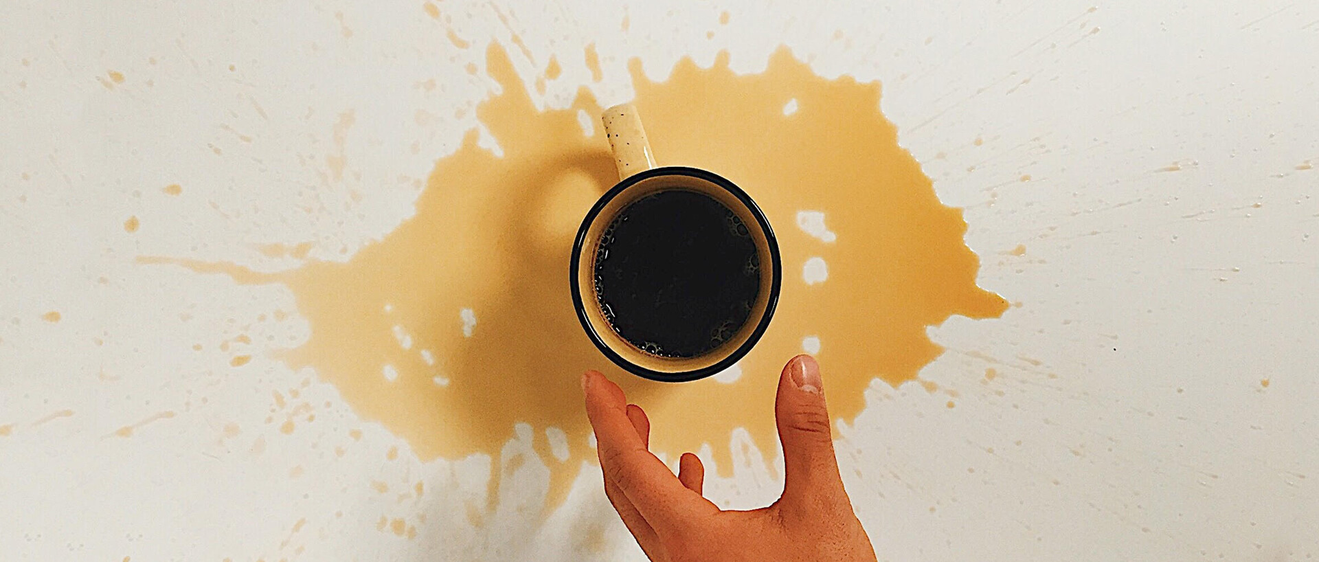 hand reaching for coffee cup that has spilled on the table