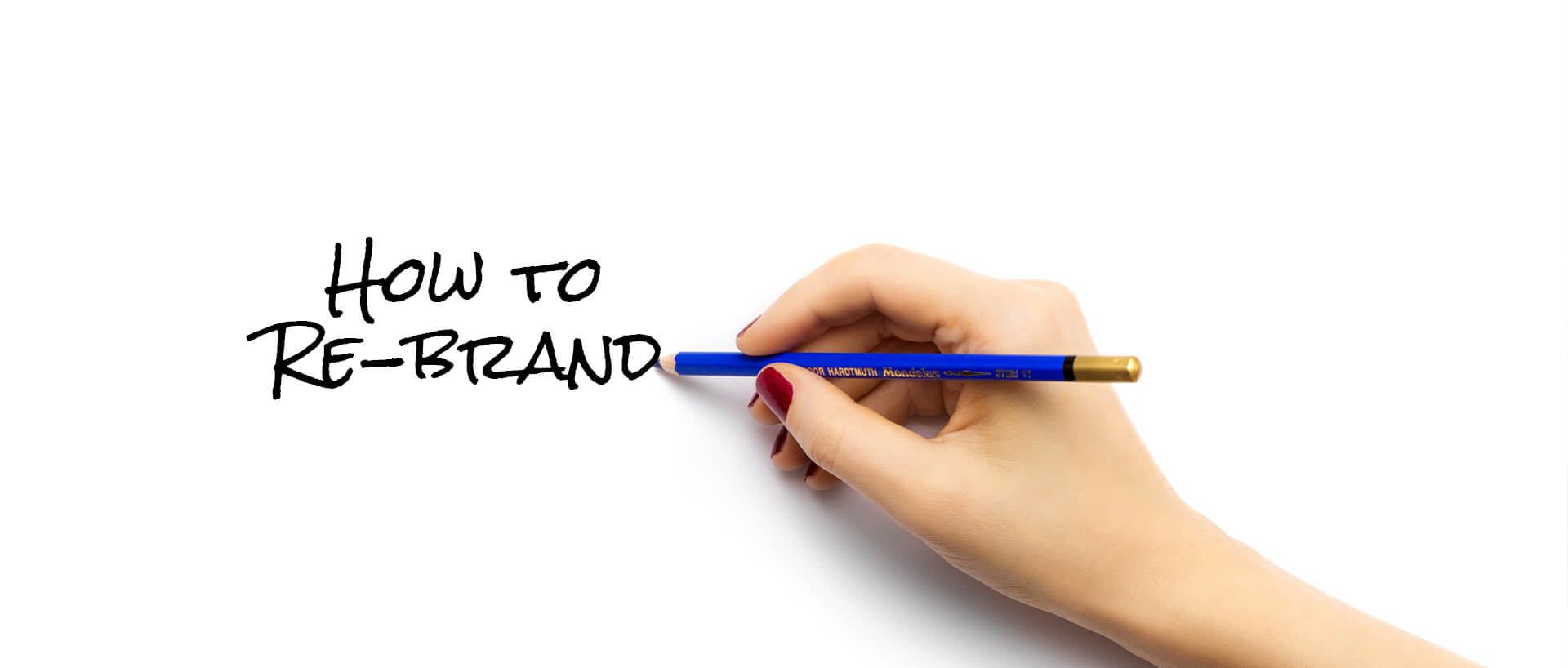 "hand holding pencil writing ""how to re-brand"""