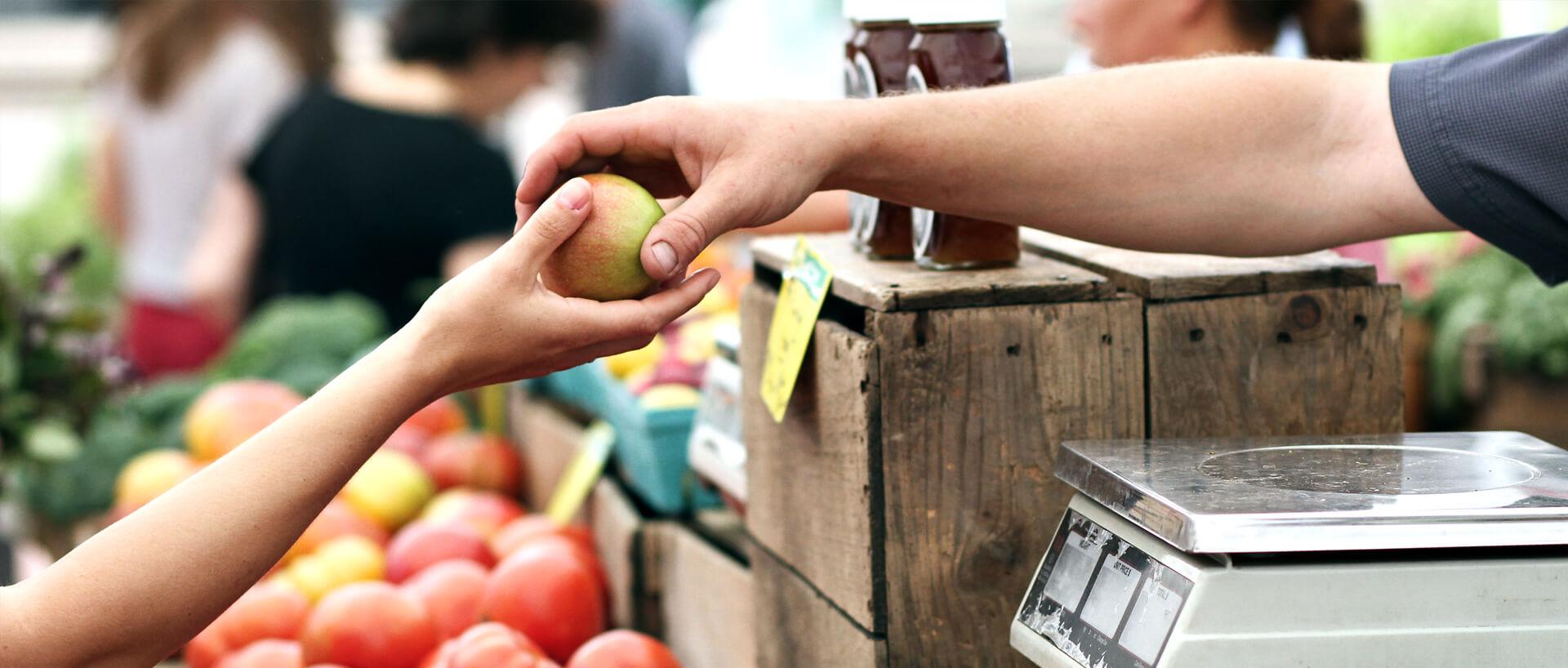 grocer handing an apple to a customer