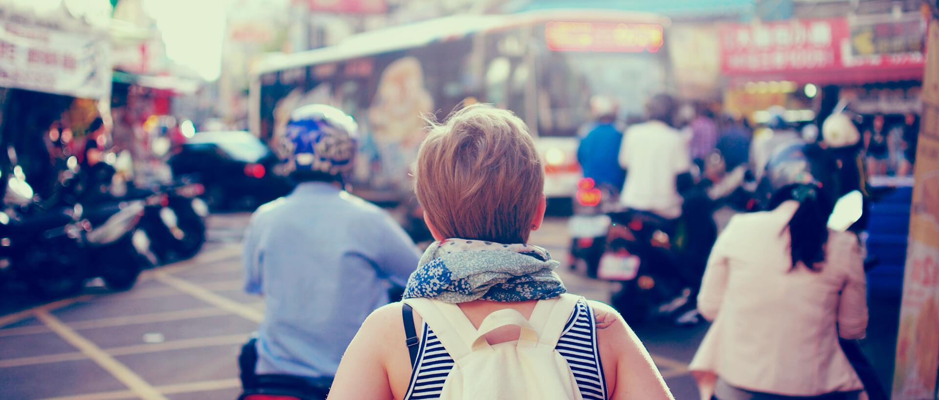 tourist backpacker walking through a busy street