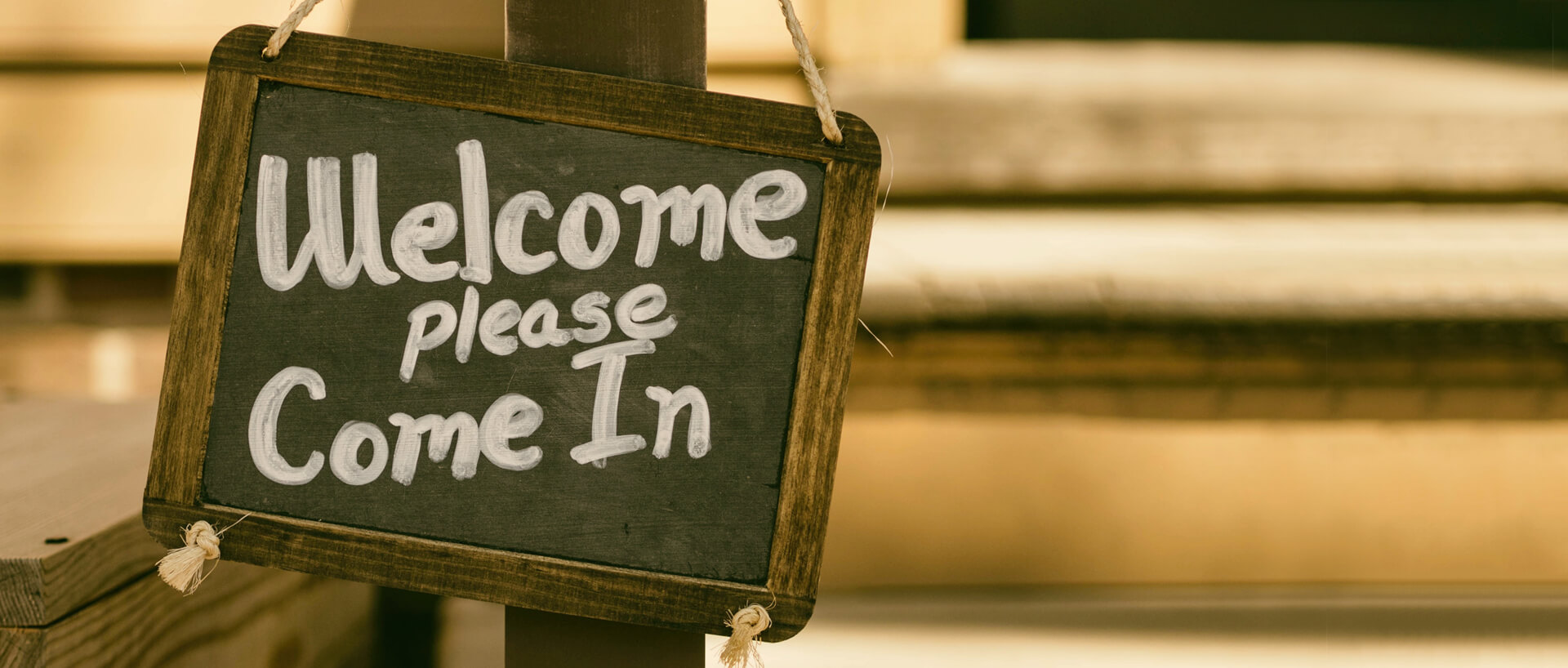 "Chalkboard business sign that reads ""Welcome, please come in"""