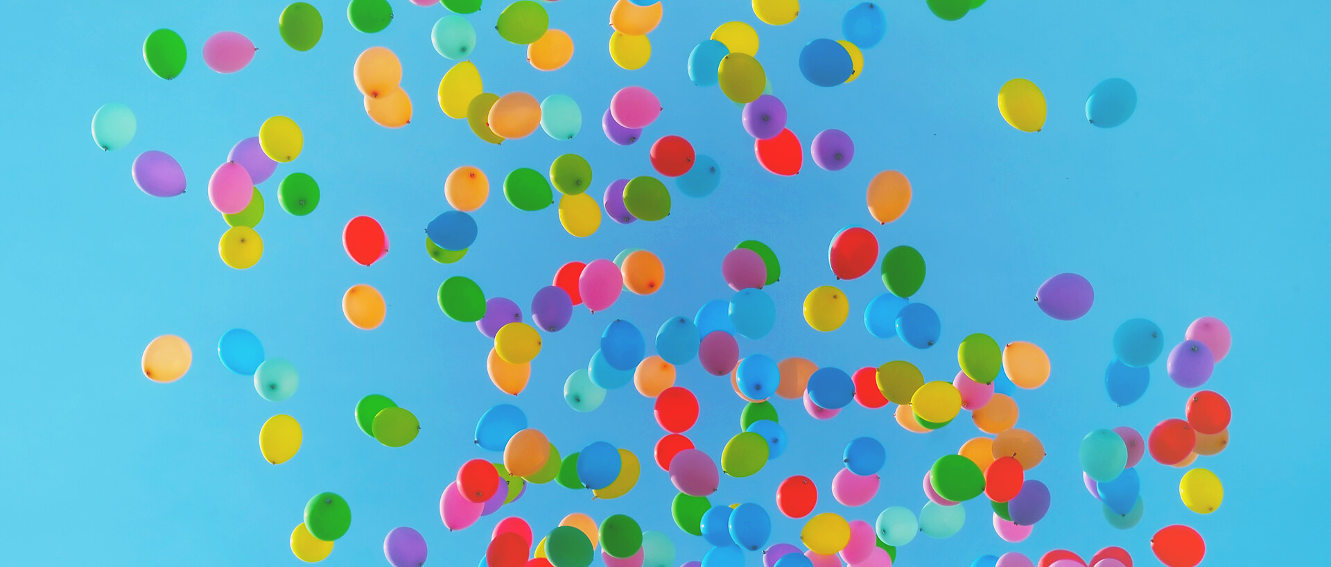 A large number of coloured balloons against a blue sky