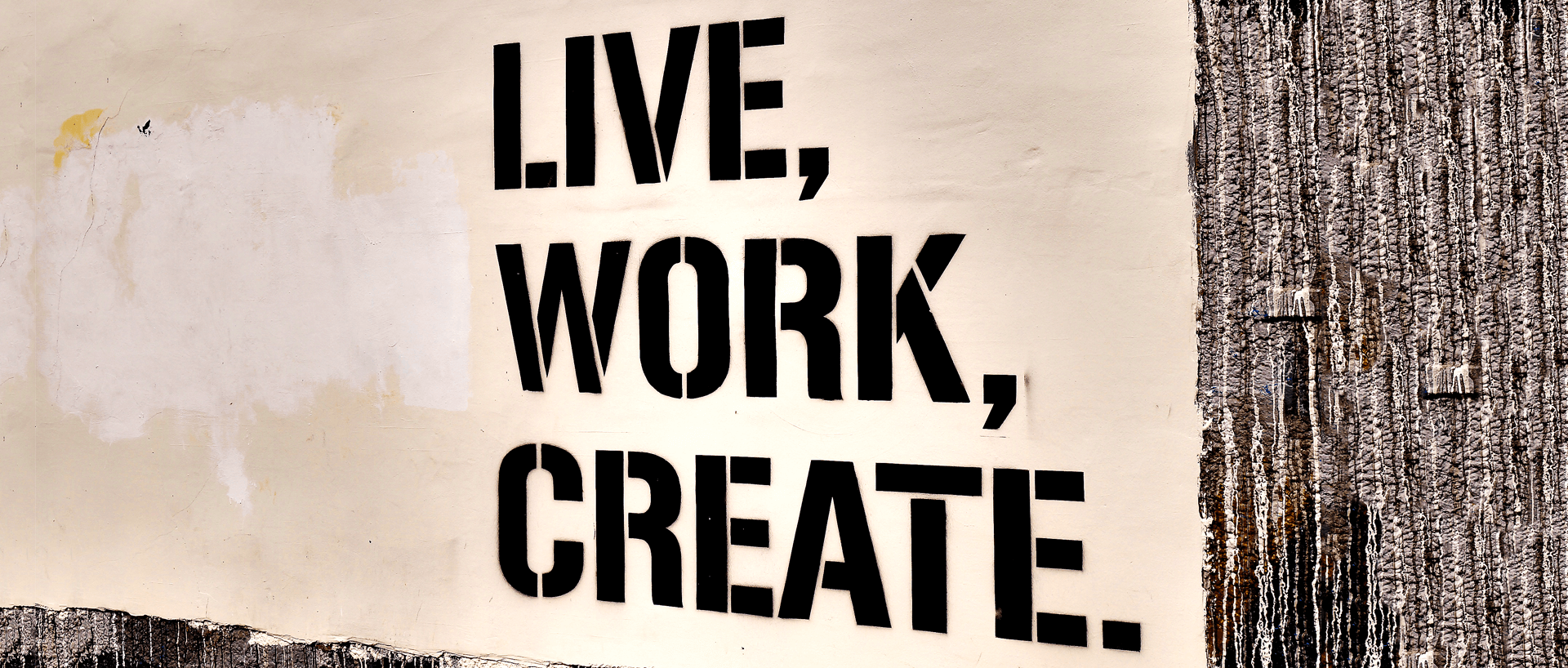 "graffiti on a wall that says ""live, work, create."""