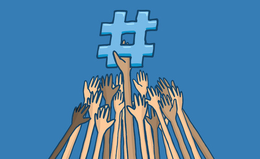 A hand holds up a hashtag symbol while a bunch of other hands try to reach for it.