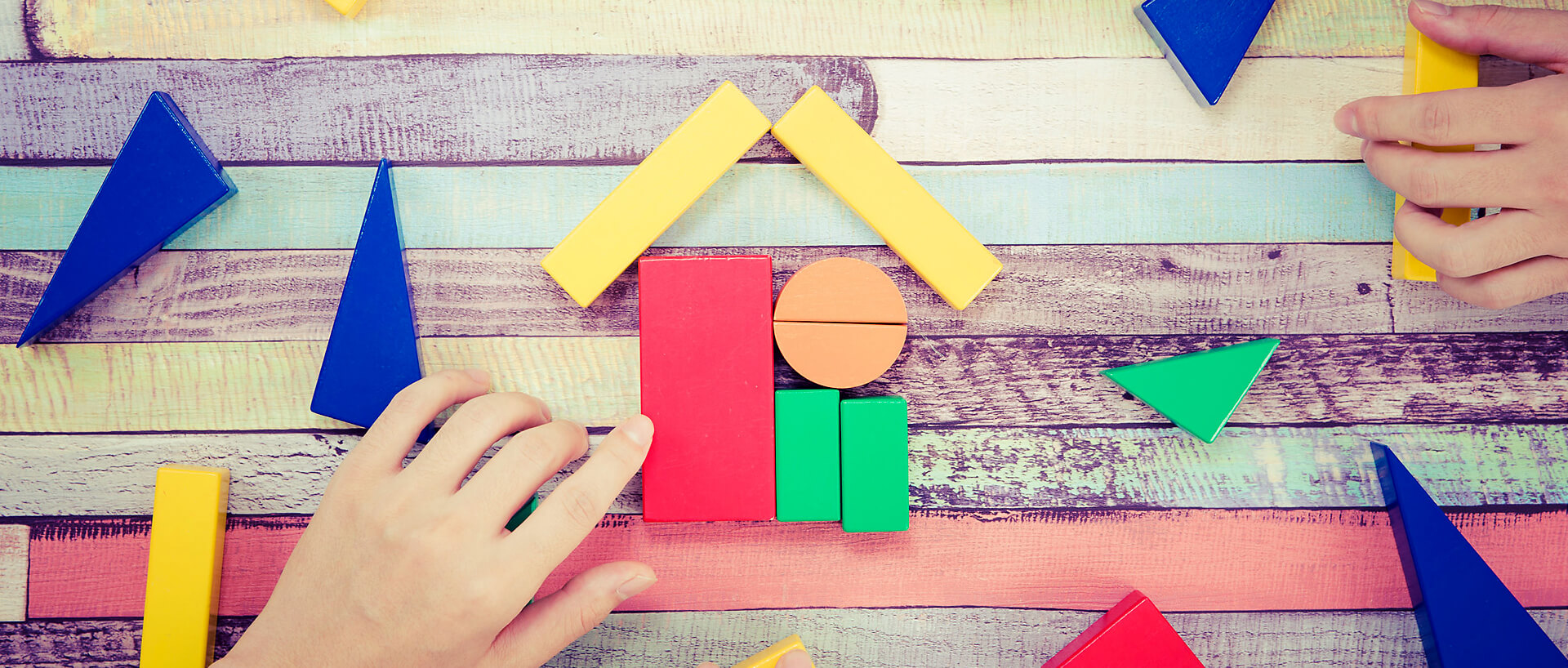 hands moving colourful building blocks into the shape of a house
