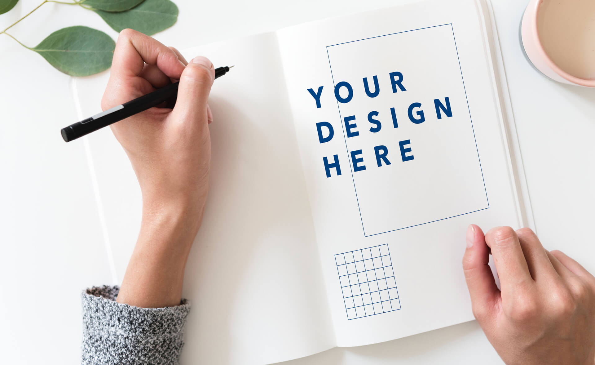 A person writes in a notebook that has a page that says 'Your Design Here'.