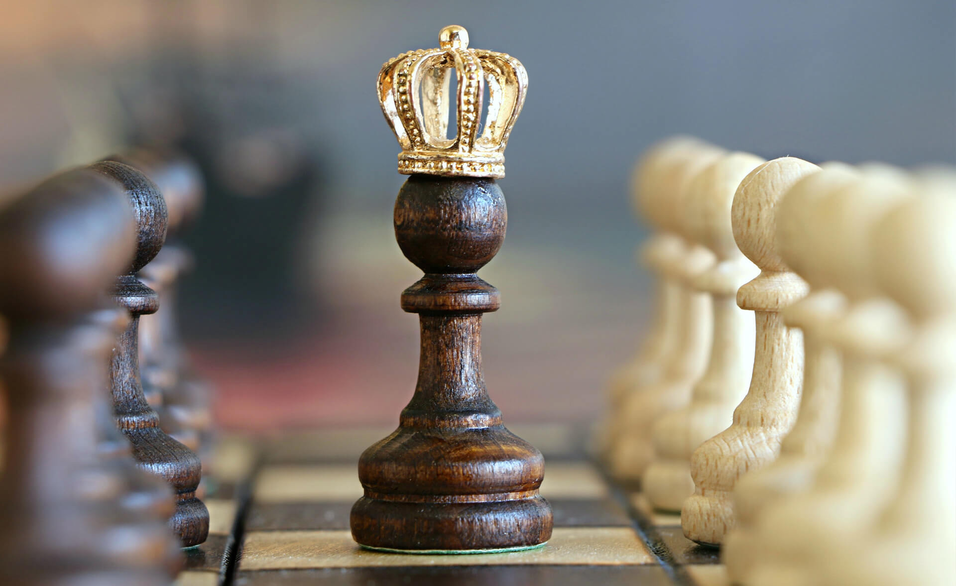 A chess pawn with a crown is in the center of a chess board, flanked by rows of other pawns