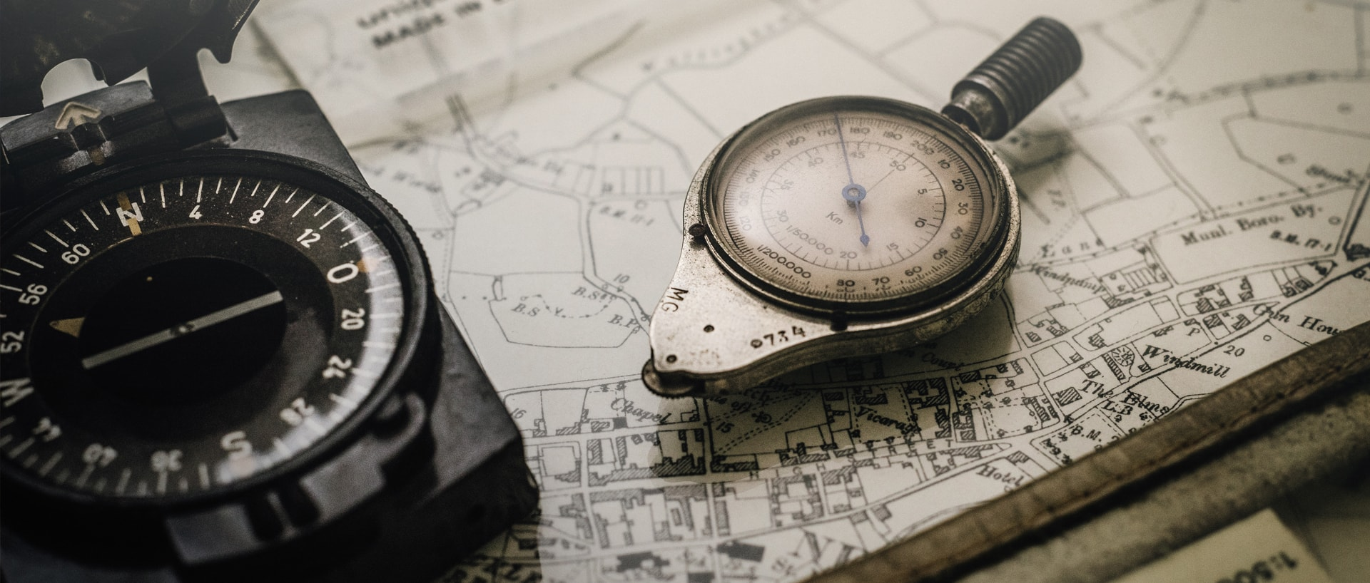 Compasses on a pile of maps and rulers